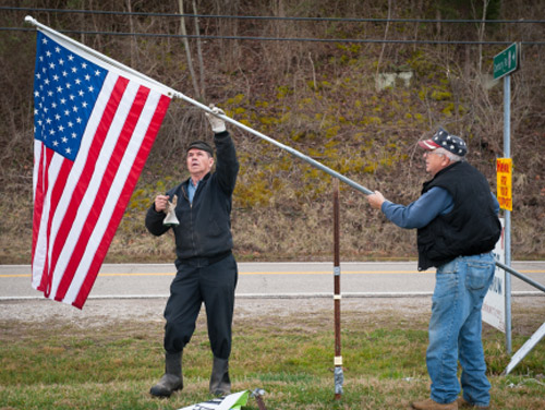 "Charles ""Smitty"" Smith (left) and Roy Dailey (right) take down the American flag at the Occupy Century Aluminum camp March 2, 2012 in Ravenswood, W. Va. Occupiers broke camp after Century caved to their demands with a $44 mil settlement to refund healthcare that will benefit 500 families in the community. The group occupied the site at the entrance to the Century Aluminum smelter for 75 days in protest of company's actions that eliminated their retiree healthcare benefits."